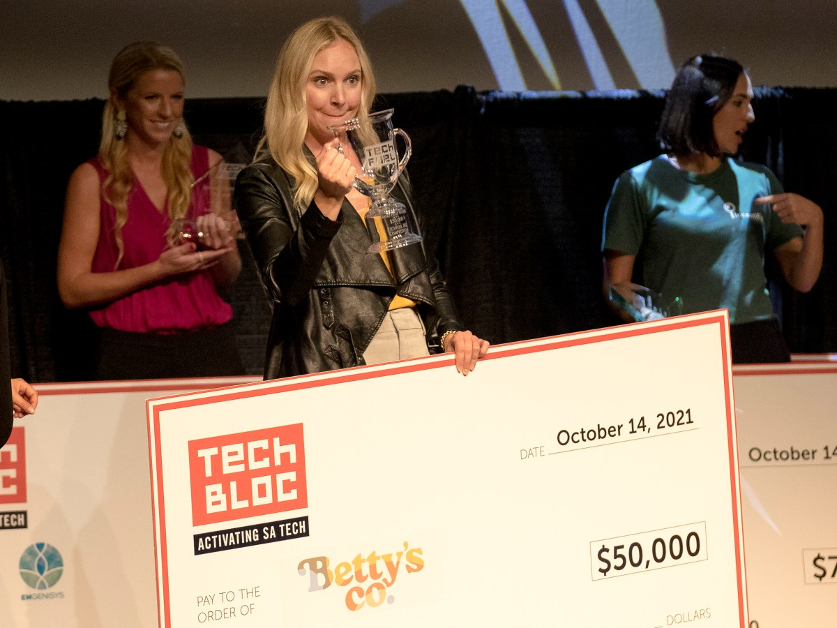Betty's Co. founder Jennifer Newell hoists a trophy while holding a $50,000 check after winning the TechFuel pitch competition on Thursday.