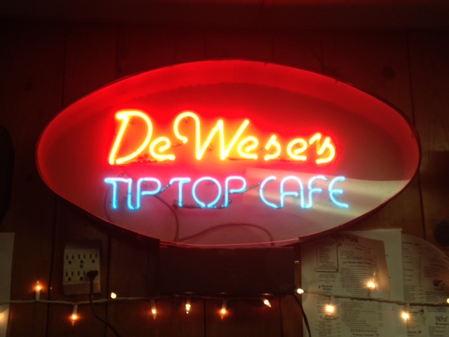 Photo of a neon sign that spells out DeWese's Tip Top Cafe.