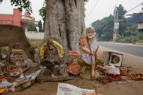 The discarded Gods give their blessings from below a tree while an old newspaper article about the high property rates in Delhi gathers dust.