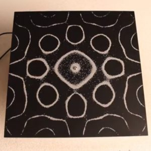 """Los patrones geométricos formados en una fina base de arena, depositada sobre una placa de vidrio o metal, vibrando a frecuencias diferentes, son llamados """"figuras sonoras de Chladni""""."""