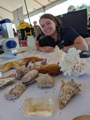 erin arneson with a table of shells and other biological artifacts