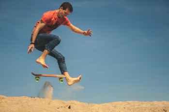 Man skateboarding on sand.