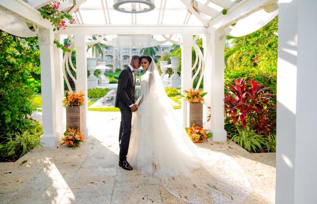 Les mariés se tiennent sous un gazebo de jardin