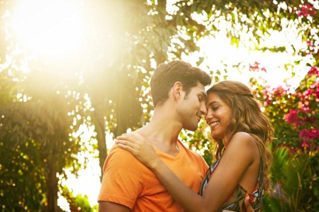 Couples souriants entourés de palmiers et de fleurs tropicales.