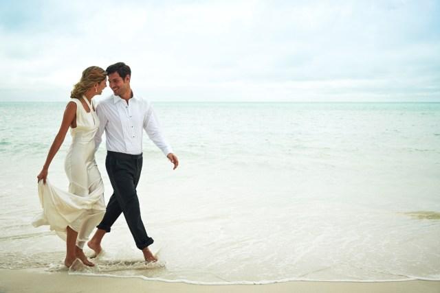 Couple marche côte à côte le long d'une plage.
