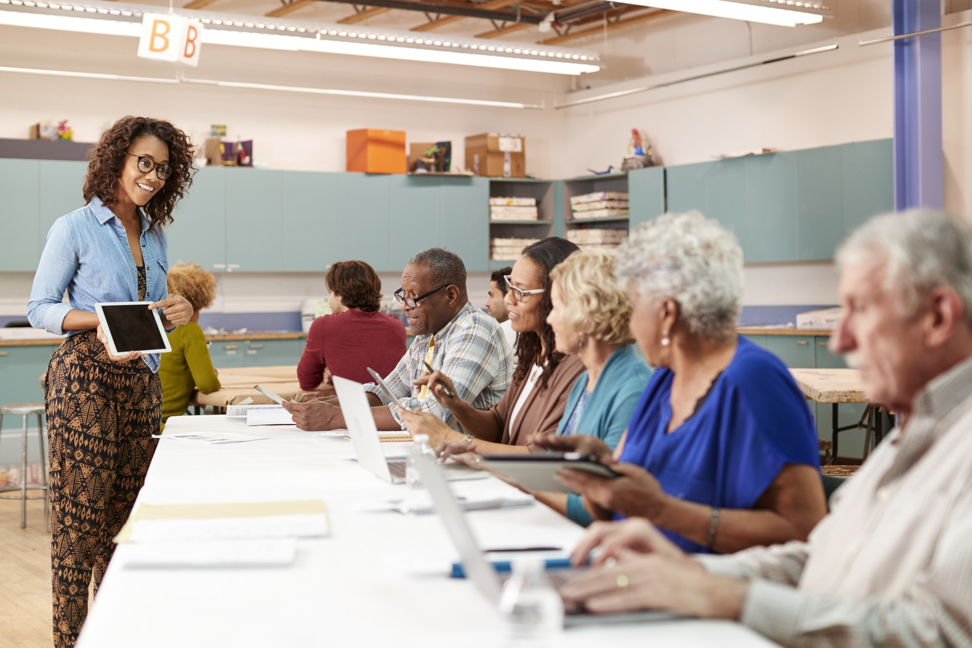Group Of Retired Seniors Attending IT Class In Community Centre With Teacher