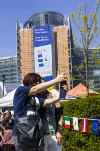 Brussels 17 May 2014. The European institutions organise their open days. The Berlaymont building, HQ of the EC shows a big banner concerning the European elections next week. The Roundpoint Schumann changed for once in a colorfull picknick zone where every country shows their agricultural products and specialities.two girls make a selfy while others eat and taste.
