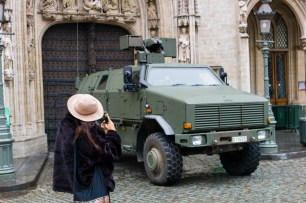 "Brussels Belgium 21 November 2015. Terror alert level for Brussels was put at 4, the maximum on a scale of 1 to 4. There is ""a very concrete and imminent threat"".A French tourist from Paris with hat takes a picture of a Belgian military vehicle at the town hall on the Big Square."