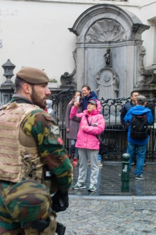 "Brussels Belgium 21 November 2015. Terror alert level for Brussels was put at 4, the maximum on a scale of 1 to 4. There is ""a very concrete and imminent threat"".The famous Belgian statue Mister pee, manneken pis, is being guarded by soldier while tourist keep on coming taking selfies"