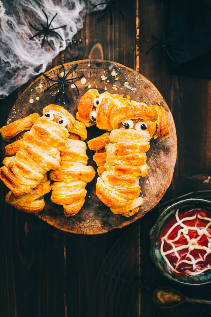 halloween sausage mummies served with ketchup on a wood background and halloween decorations