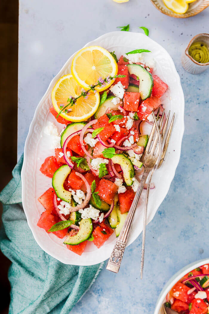 Watermelon Salad with cucumber, onion and crumbled feta served in an oval platter