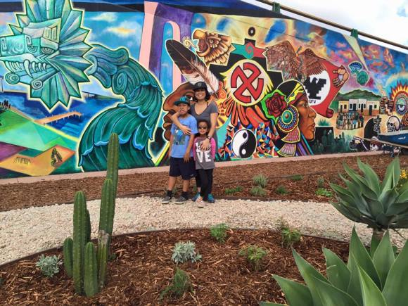 Woman with two children in front of Chicano Park mural by herb garden