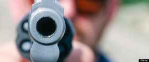 Guns; robbery. A man points a handgun directly at the camera.