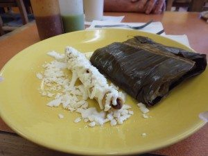 Rolled lamb taco and tamal in banana leaf