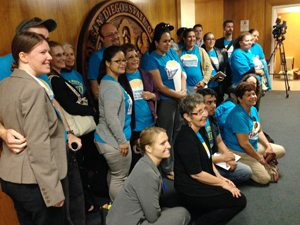 Members of the Environmental Health Coalition pose for a photo after the Barrio Logan plan passes.