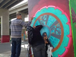 Artists Cesar Castañeda and Patricia Aguayo work on their mural of Chicano Park Steering Committee chairperson Tommie Camarillo.