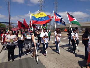 Marchers flying the flags of Unión del Barrio, Colombia, Cuba and South Africa among others.