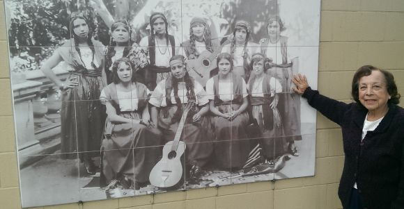 Mary Barrios with mural of Singing Mothers