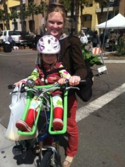 Woman with child on bike with special child carrier