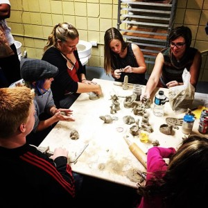 Group sitting around square table and working on ceramics