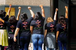 """Group of six women displaying back of their T-shirts with statement """"The PERSONAL IS POLITICAL"""" and with fists raised in power salute at the International Women's Day celebration, Los Angeles, CA, March 5, 2016."""