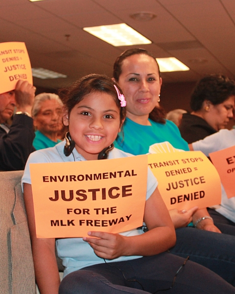 Group with MLK freeway environmental justice signs