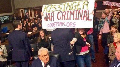 """Code Pink activists with """"Kissinger War Criminal"""" banner behind seated Kissinger"""