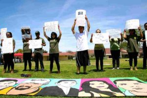 At MiraCosta College, students hold handmade signs to protest in silence before the Border Patrol recruiters.