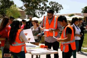 At MiraCosta College career fair, students in orange safety jackets conduct a Border Reality Checkpoint to inform others of their rights.