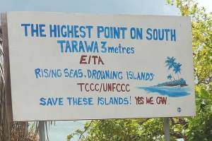"""Hand painted sign calling attention to threat of rising sea level to South Tarawa and plea to """"Save these islands!"""""""