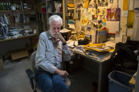 Professor Emeritus Fred Lonidier ; sitting at his desk in the Visual Arts Department, UCSD