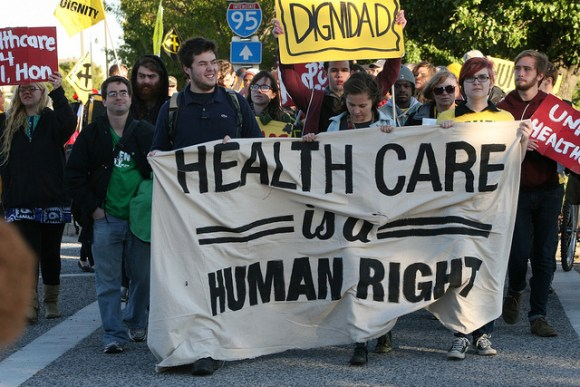 """Protest marchers with banner: """"Health Care is a Human Right"""""""