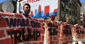 "Protestors wearing ""Wall Off Trump"" signs"