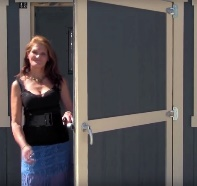Woman standing in doorway holding door open