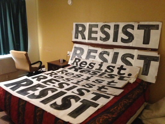 """RESIST"" posters arrayed on motel bed"