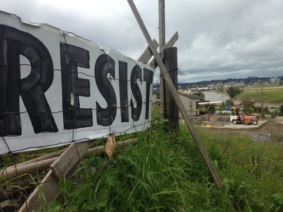 "Close up side view of ""RESIST"" banner along side of freeway"