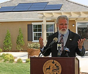 Lancaster mayor Rex Parr speaking at lectern in front of house with solar panels on roof