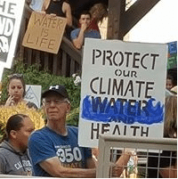 Person holding sign: Protect Our Climate, Water and Health