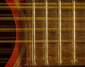 Close up of the neck of an acoustic guitar near the soundhhole with vibrating strings