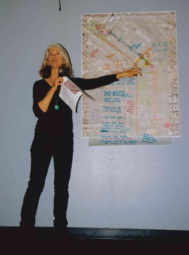Woman pointing to urban planning map on wall