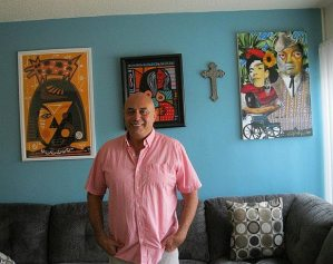 Herbert standing in room with artwork on wall behind him.