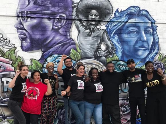 Group of people gathered in front of mural