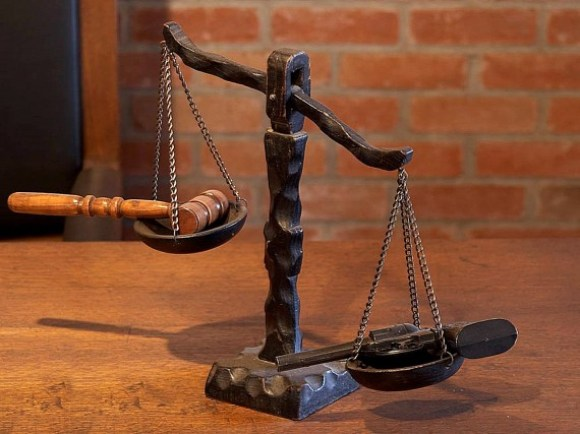 Scales of Justice, with a handgun outweighing a gavel