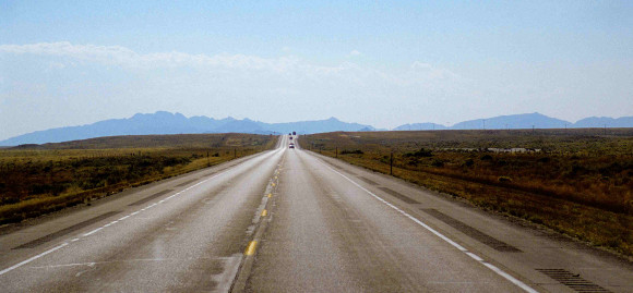 View of two lane highway stretching off to the horizon, mountain range in distance