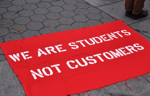 "Banner on ground reading ""WE ARE STUDENTS NOT CUSTOMERS"""