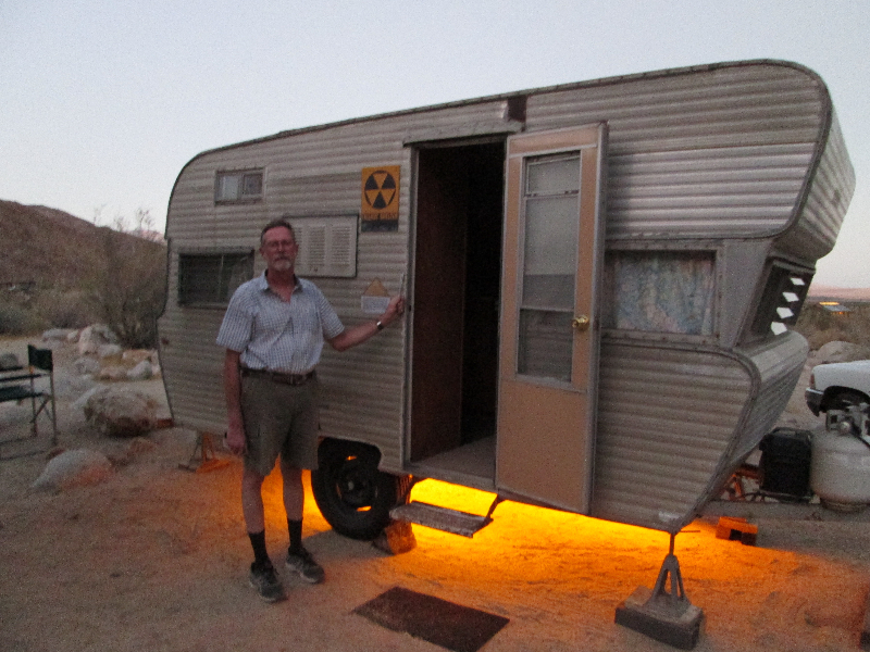 Man standing in front of mobile camper with glowing light undrneath, desert campground location