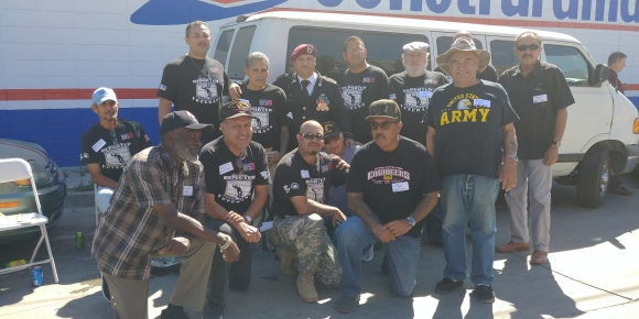 Group of about fourteen veterans posing for camera in a parking lot in front of a van.