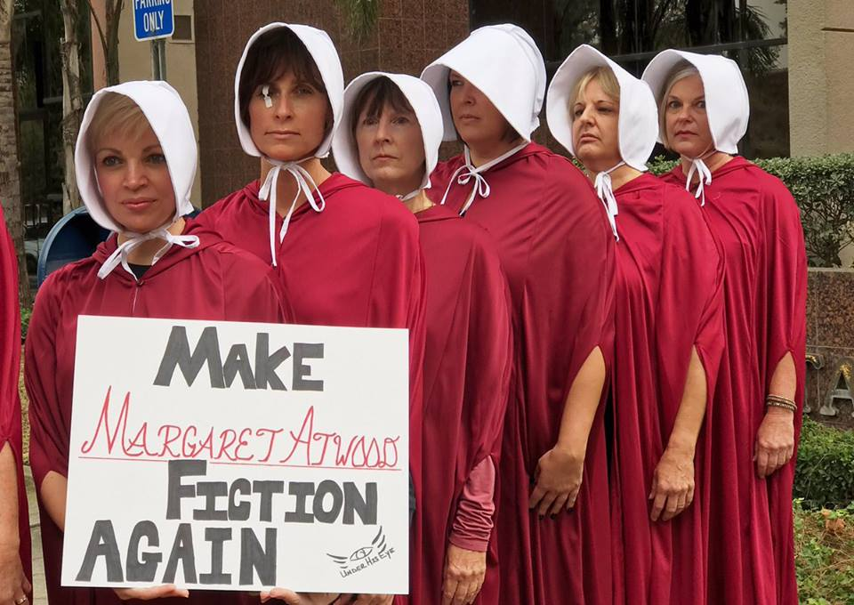 """Women dressed as characters from """"The Handmaid's Tale"""" holding sign """"Make Margaret Atwood Fiction Again"""""""