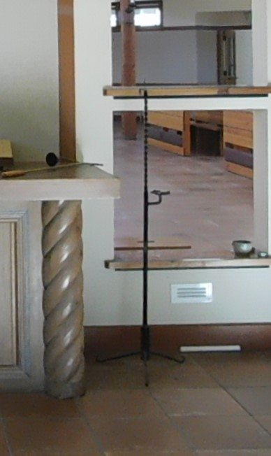 Wrought iron candelabra standing next to marble altar