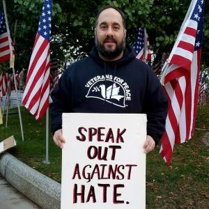 "Man wearing Veterans for Peace pullover, standing in front of American flags and holding sign that reads ""SPEAK OUT AGAINST HATE"""